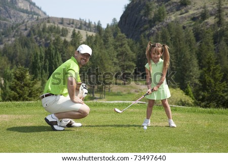 Outdoor photo of father and youngster daughter on golf course.