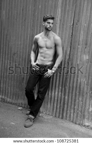 Outdoor photo of handsome, shirtless young man standing against grunge metal wall. - stock photo