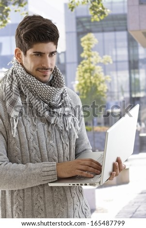 Outdoor photo of handsome young man holding laptop computer, smiling. - stock photo