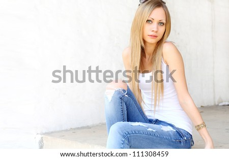 Outdoor photo of pretty girl sitting on the floor in grungy setting. - stock photo