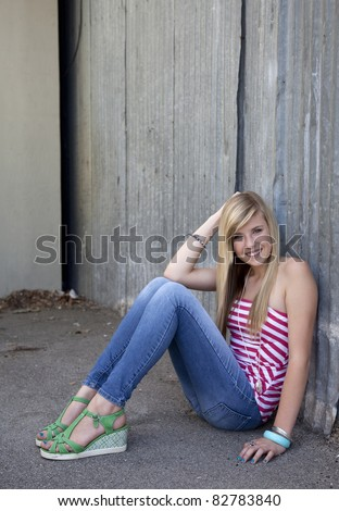 Outdoor photo of pretty teenage girl sitting on the ground in grungy setting.