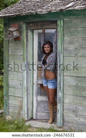 Outdoor photo of pretty young woman dressed in 60's clothes in cabin doorway.