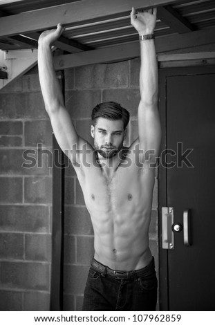 Outdoor photo of shirtless, attractive young man looking at camera. - stock photo