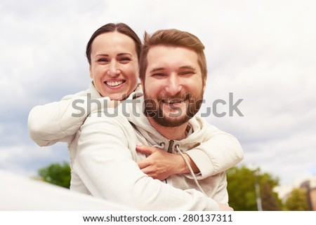 outdoor photo of smiley couple in love looking at camera and laughing - stock photo