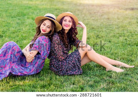 Outdoor  photo of two best friends   posing   on green meadow and  enjoy time together. Wearing straw hat and colorful boho dress. Summer sunny day. - stock photo