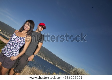 Outdoor photo of young, attractive couple hiking with mountains and lake in background.