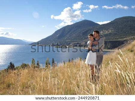 Outdoor photo of young couple embracing in grassy field at scenic viewpoint - stock photo