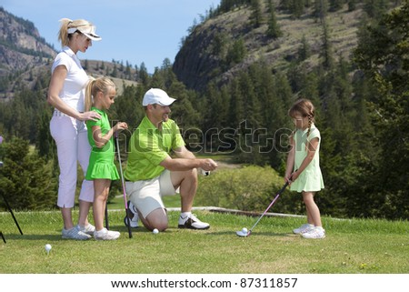 Outdoor photo of young family of four on golf course, father is instructing child. - stock photo