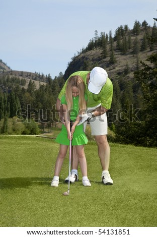 Outdoor photo of young girl at golf lesson. - stock photo
