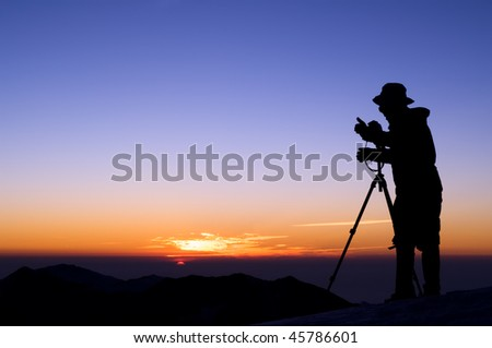 Outdoor photographer silhouette with dramatic color sunrise. - stock photo