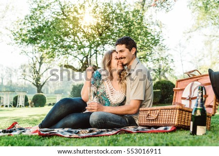Outdoor picnic by couple that are enjoying a glass of Sparkling wine while relaxing in nature