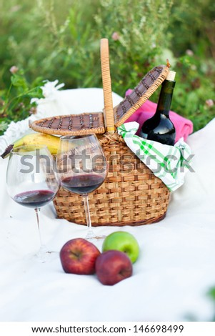 Outdoor picnic setting with red wine and fruits - stock photo