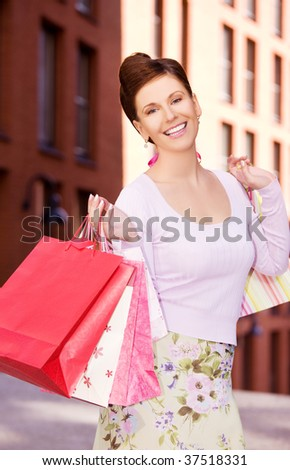 outdoor picture of happy woman with shopping bags