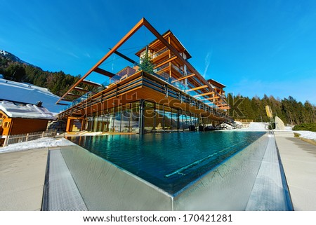 outdoor pool which is steaming at a cold and clear winter day and mountains in the background - stock photo