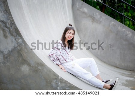 outdoor portrait Asian  girl smile with Skate Board ramp