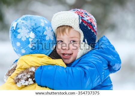 Outdoor portrait child hugs his mother in winter park - stock photo