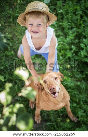 Outdoor portrait:   Handsome Young Boy and His Dog looking up - stock photo