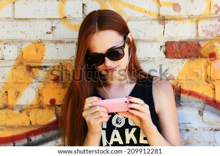 outdoor portrait hipster redhead woman using a smart phone graffity wall - stock photo