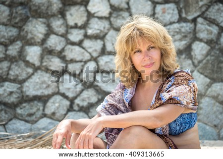 outdoor portrait of a beautiful adult woman in swimsuit and scarf over her shoulders sitting against stone wall - stock photo
