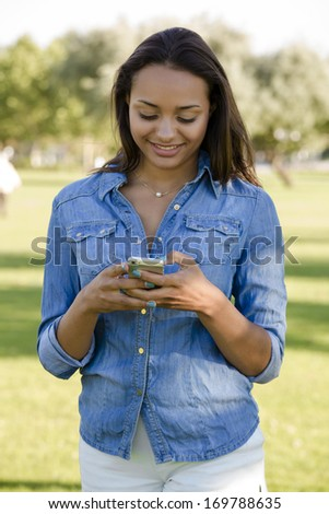 Outdoor portrait of a beautiful African American sending a sms