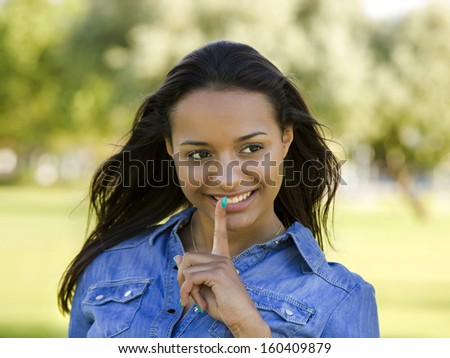 Outdoor portrait of a beautiful African American woman asking silence - stock photo