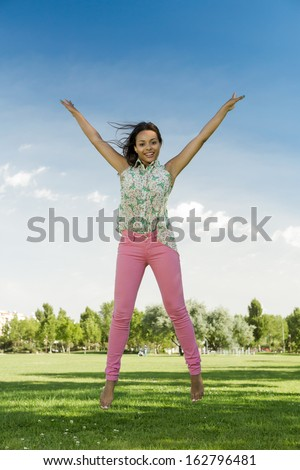 Outdoor portrait of a beautiful African American woman jumping - stock photo