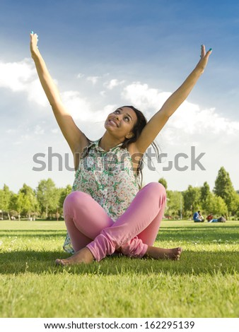 Outdoor portrait of a beautiful African American woman sitting on the grass with arms open - stock photo