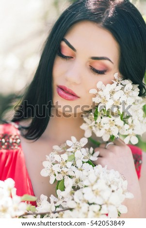 Outdoor Portrait of a Beautiful Brunette Woman in Color dress among Blossom Cherry Trees
