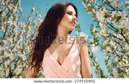 outdoor portrait of a beautiful brunette woman in pink dress among blossom cherry trees. Fashion photo - stock photo