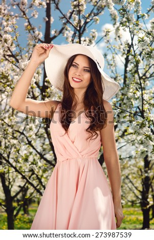 outdoor portrait of a beautiful brunette woman in pink dress, summer hat among blossom apple trees - stock photo