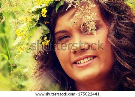 Outdoor portrait of a beautiful girl in the wreath