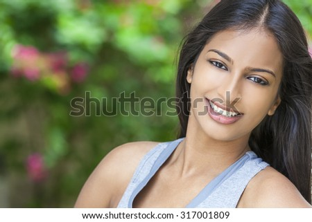 Outdoor portrait of a beautiful Indian Asian young woman or girl outside in summer sunshine with perfect teeth and long hair - stock photo