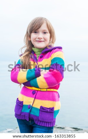 Outdoor portrait of a beautiful little girl in colorful jacket