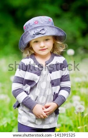 Outdoor portrait of a beautiful little girl in summer field - stock photo