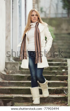 Outdoor portrait of a beautiful long-haired blond young woman wearing a white coat and white boots, walking down the stairs on a cold winter day. Shallow depth of field. - stock photo