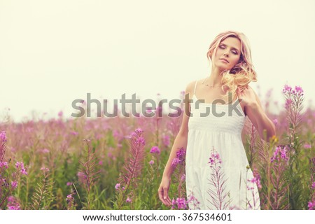 outdoor portrait of a beautiful middle aged blonde woman. attractive sexy girl in a field with flowers - stock photo