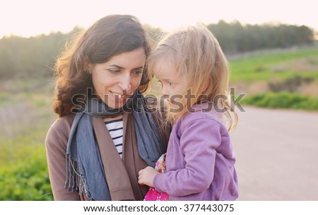 outdoor portrait of a beautiful middle aged mother and daughter