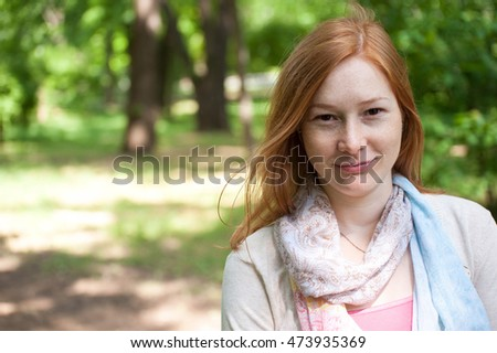 Outdoor portrait of a beautiful redhead woman