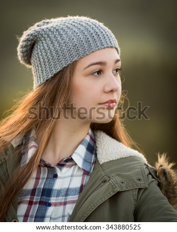 Outdoor portrait of a beautiful teenage girl with ginger long hair wearing a warm coat and a woolly hat looking.