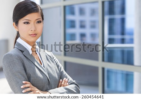 Outdoor portrait of a beautiful young Asian Chinese woman or businesswoman in smart business suit - stock photo