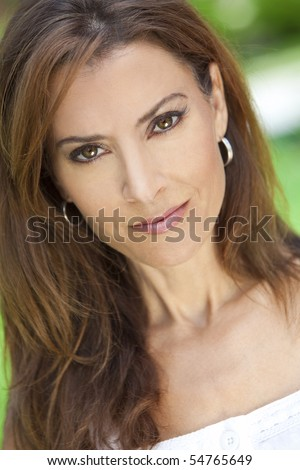 Outdoor portrait of a beautiful young brunette woman in her thirties - stock photo