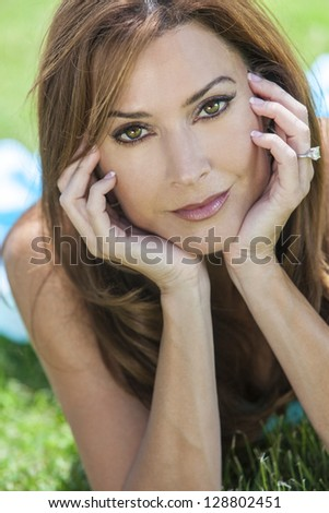 Outdoor portrait of a beautiful young brunette woman in her thirties relaxing on her hands. - stock photo