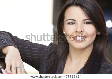 Outdoor portrait of a beautiful young Latina Hispanic woman or businesswoman smiling - stock photo