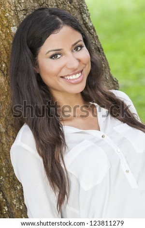 Outdoor portrait of a beautiful young Latina Hispanic woman smiling leaning against a tree