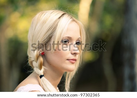 Outdoor portrait of a beautiful young woman in the park - stock photo