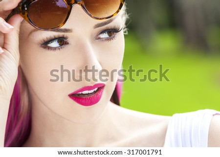 Outdoor portrait of a beautiful young woman or girl with brown eyes, blond and magenta pink hair wearing sunglasses - stock photo