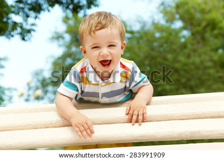 outdoor portrait of a boy on green background. happy child on walk in the summer park - stock photo