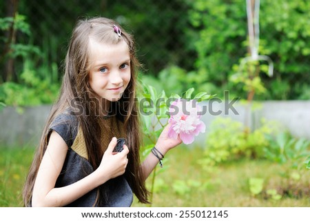 Outdoor portrait of a charming young brunette girl with pink peony with water drops after rain - stock photo