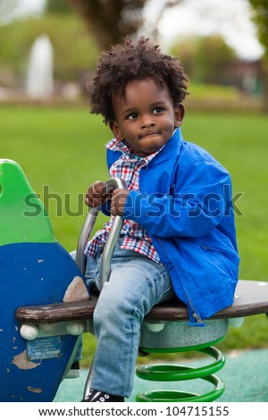 Outdoor portrait of a cute  black baby boy playing at playground - stock photo