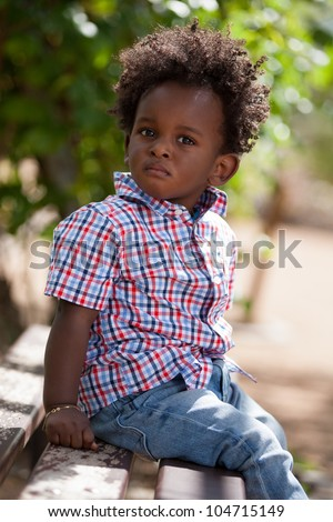 Outdoor portrait of a cute black baby boy sited on a bench